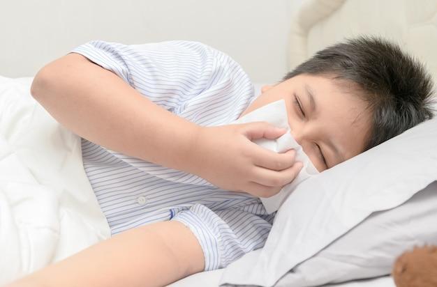 Zieke jongen die de neus blaast door weefsel