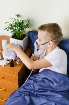 Zieke jongen die door vernevelaar, inhalator ademt voor behandelingspreventie.