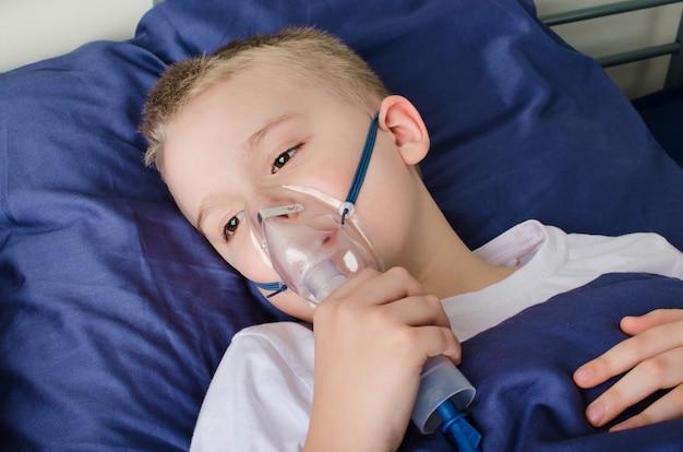 Zieke jongen die door verstuiver ademt