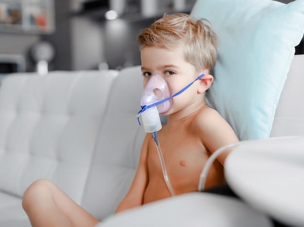 Zieke jongen die in verstuiversmasker inhalatie maakt
