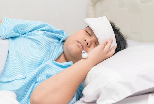 Zieke jongen met thermometer in mond en kompres op voorhoofd.