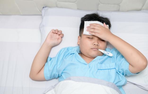Zieke jongen met thermometer in mond