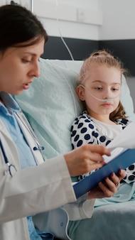 Zieke kindpatiënt die zuurstofneusbuis draagt die in bed rust die herstelt na ademhalingsziektechirurgie tijdens medisch overleg. arts-vrouw arts analyseert ziekte-expertise in ziekenhuisafdeling
