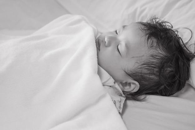 Zieke kindslaap op de geweven achtergrond van het het ziekenhuisbed in zwart-witte toon