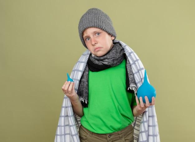 Zieke kleine boyin warme muts en sjaal gewikkeld in deken met klysma's loking verward en ontevreden staande over lichte muur