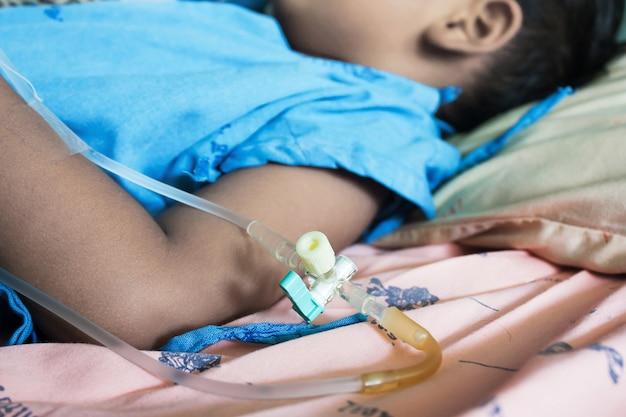 Zieke kleine jongen liggend in een ziekenhuis iv.