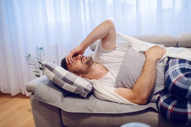 Zieke knappe blanke man in pyjama liggend op de bank in de woonkamer en buikpijn.