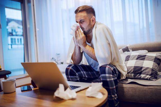 Zieke knappe ongeschoren blanke man in pyjama bedekt met deken zittend op de bank in de woonkamer en zijn neus snuiten.