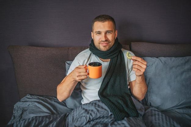 Zieke maar positieve jonge man zit op bed in de slaapkamer en kijkt op camer. hij houdt een oranje beker in de ene hand en een stukje citroen in een andere. guy lacht. hij ziet er gelukkig uit.
