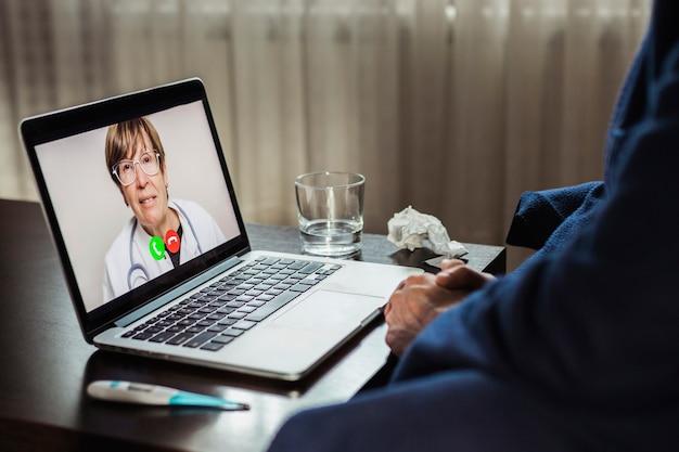 Zieke man chatten met dokter tijdens video-oproep tijdens isolatie quarantaine. gezondheidszorg en medisch concept