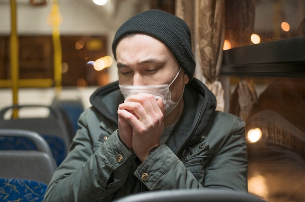 Zieke man die in de bus hoest terwijl hij een medisch masker draagt