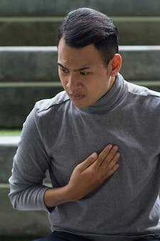 Zieke man die lijdt aan zure reflux, brandend maagzuur