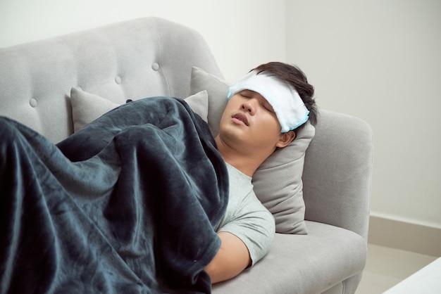 Zieke man die op de bank ligt en zijn temperatuur controleert onder een deken thuis in de woonkamer