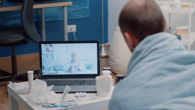 Zieke man die telegeneeskunde voor videogesprekken gebruikt voor overleg