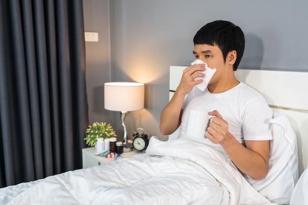 Zieke man drinken van een kopje warm water op bed