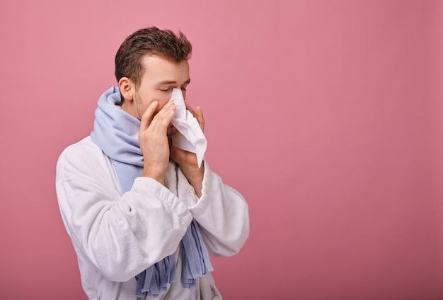 Zieke man in blauwe sjaal en witte robe staat bevroren en blaast zijn neus in servet