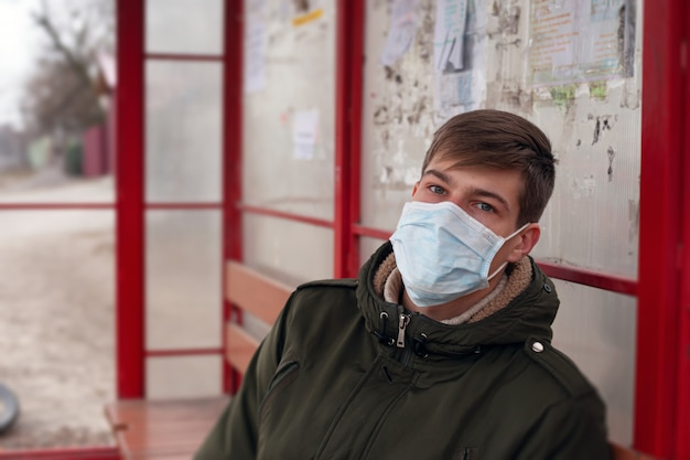 Zieke man in een busstation, beschermd tegen het chinese virus op openbare plaatsen.