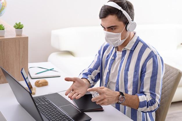 Zieke man in medisch masker en koptelefoon op laptop desinfecteert zijn handen met ontsmettingsmiddel, extern werk in quarantaine, freelancer concept