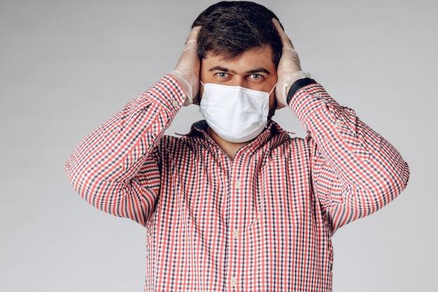 Zieke man in medisch masker op gezicht en beschermende handschoenen op handen hoofdpijn voelen.