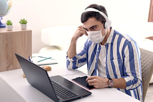 Zieke man in medische masker en koptelefoon bezig met laptop, extern werk in quarantaine thuis, freelancer concept