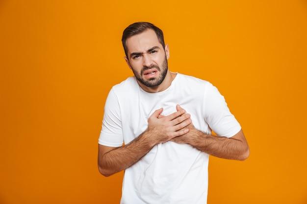 Zieke man in t-shirt zijn hart aanraken vanwege pijn terwijl, geïsoleerd op geel