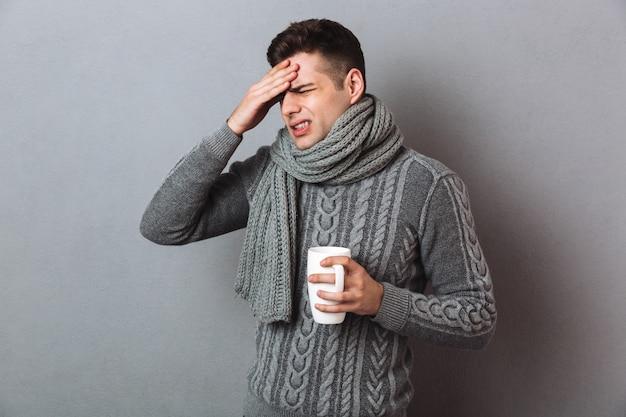 Zieke man in trui en sjaal met hoofdpijn terwijl kopje thee