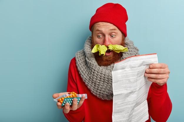 Zieke man in warme kleren met papieren zakdoekjes en pillen