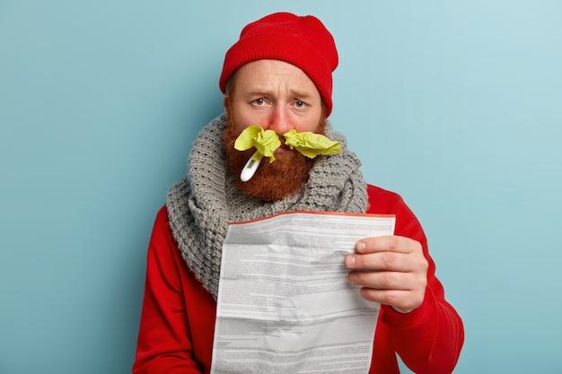 Zieke man in warme kleren met papieren zakdoekjes en thermometer