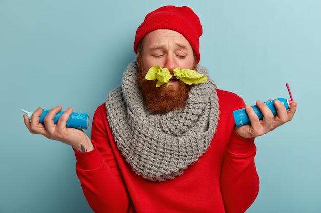 Zieke man in warme kleren met papieren zakdoekjes in de neus en spray voor keelpijn