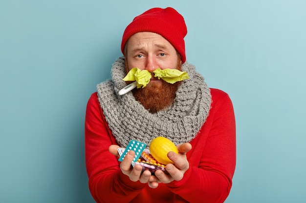 Zieke man in warme kleren met papieren zakdoekjes in neus en pillen