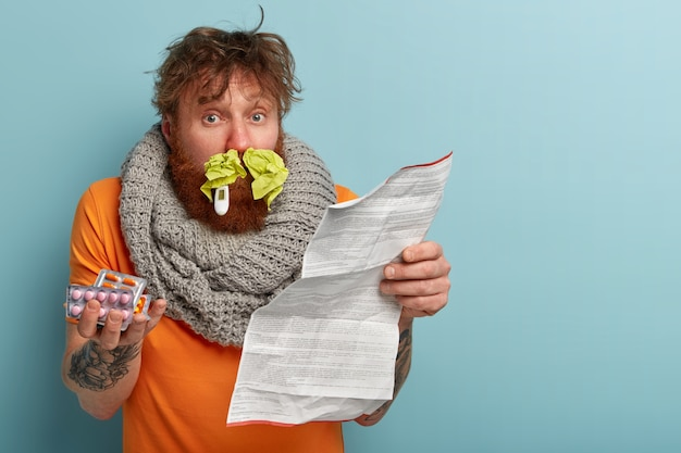 Zieke man in warme kleren met papieren zakdoekjes in neus en thermometer