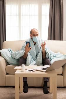 Zieke man in zijn appartement die voorgeschreven medicijnen controleert bij zijn arts.