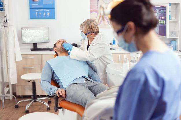 Zieke man liggend in stomatologie stoel met open mond voor medisch onderzoek