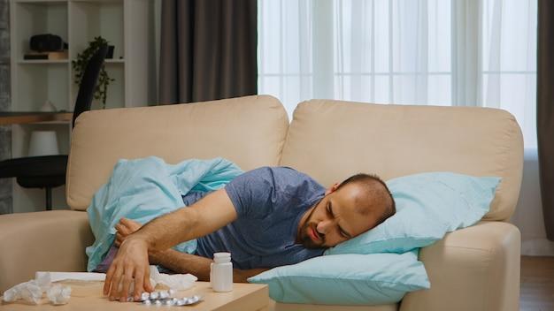 Zieke man liggend op de bank bedekt met deken tijdens wereldwijde pandemie.