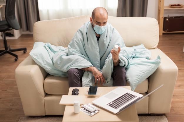 Zieke man met beschermingsmasker met pillenfles gewikkeld in een deken die recept leest