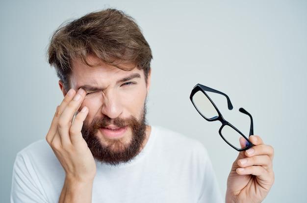 Zieke man met bril in de hand zichtproblemen lichte achtergrond
