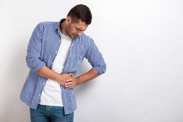 Zieke man met een buikpijn, die maag aan zijn maag houdt