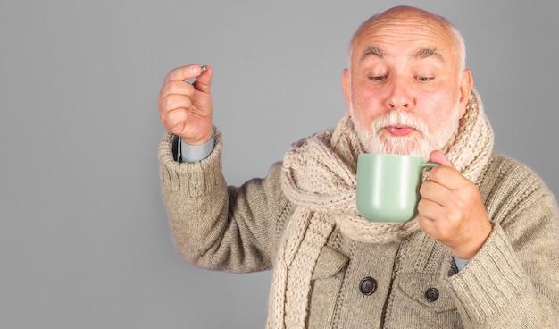 Zieke man met helende thee en farmaceutische pillen. zieke man neemt pil. medicijn. behandeling.