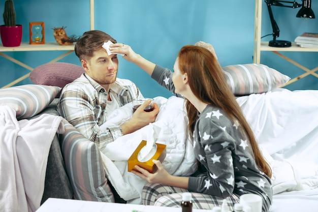 Zieke man met koorts liggend in bed met temperatuur. zijn vrouw zorgt voor hem. de ziekte, griep, pijn, familieconcept. ontspanning thuis. gezondheidszorgconcepten.