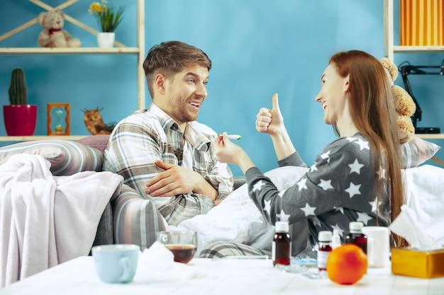 Zieke man met koorts liggend in bed met temperatuur. zijn vrouw zorgt voor hem. de ziekte, griep, pijn, familieconcept. ontspanning thuis