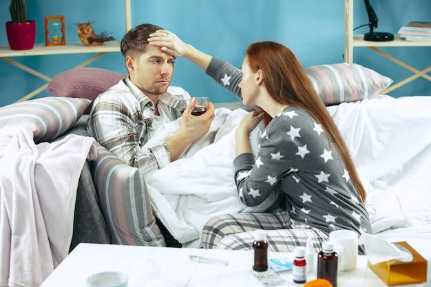 Zieke man met koorts liggend in bed met temperatuur. zijn vrouw zorgt voor hem.