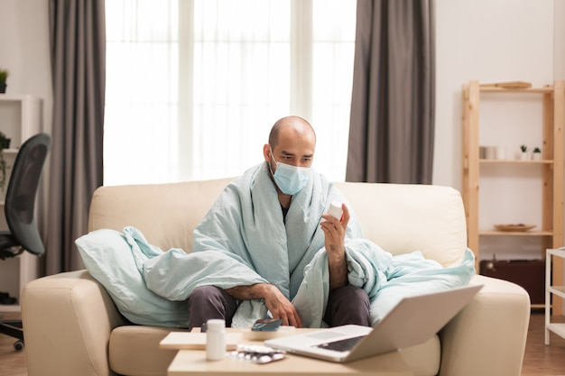 Zieke man met koorts tijdens quarantaine op zoek naar recept voor pillen op internet met behulp van laptop.