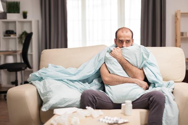 Zieke man met koude rillingen verpakt in blacket tijdens quarantaine.