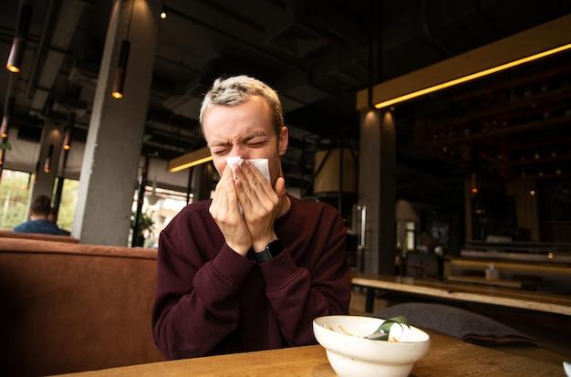 Zieke man met loopneus kwam naar een café. blijf thuis concept.