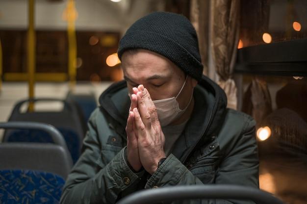 Zieke man met medische masker bidden in de bus