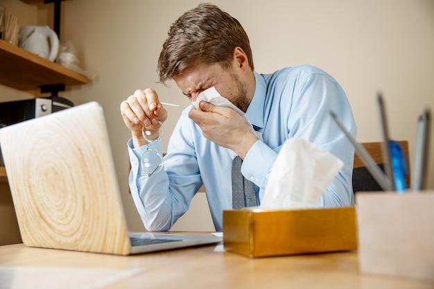 Zieke man met zakdoek niezen snuiten neus tijdens het werken in kantoor, zakenman verkouden, seizoensgriep.