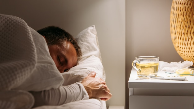 Zieke man slaapt in bed met hoge koorts, lijden aan griep, kopje thee met citroen op tafel