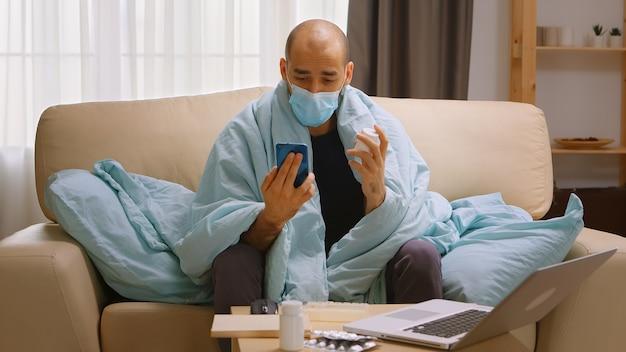 Zieke man tijdens een videogesprek met arts tijdens covid-isolatie, pratend over zijn voorgeschreven medicijn