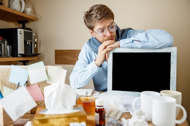 Zieke man tijdens het werken op kantoor met seizoensgriep.