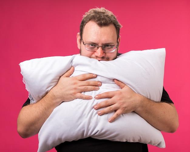 Zieke man van middelbare leeftijd knuffelde kussen geïsoleerd op roze muur